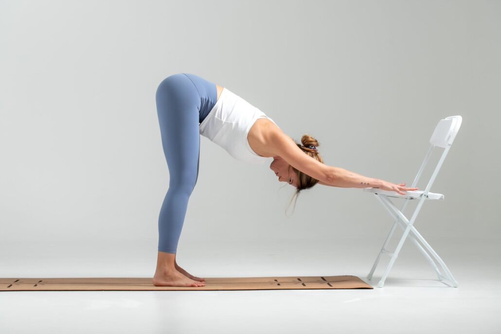 Practicing Downward Dog Pose on the back of a chair or a railing