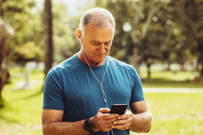 Senior man in fitness wear checking his mobile phone during workout. Portrait of a senior fitness man standing in park listening to music while working out.